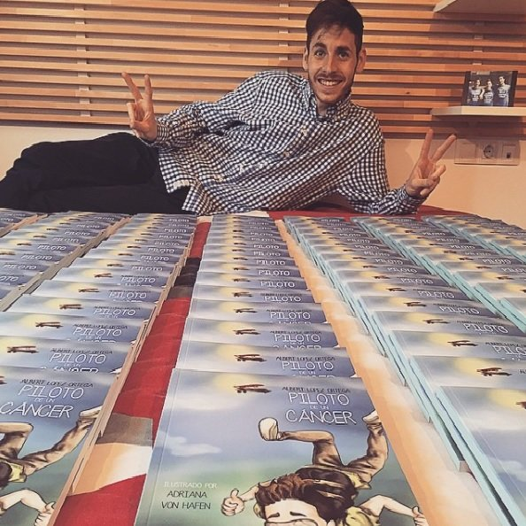 "Albert posing with some copies of ""Piloto sobre un cáncer""."