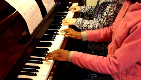 Alumnas tocando el piano a cuatro manos durante una actividad de clase