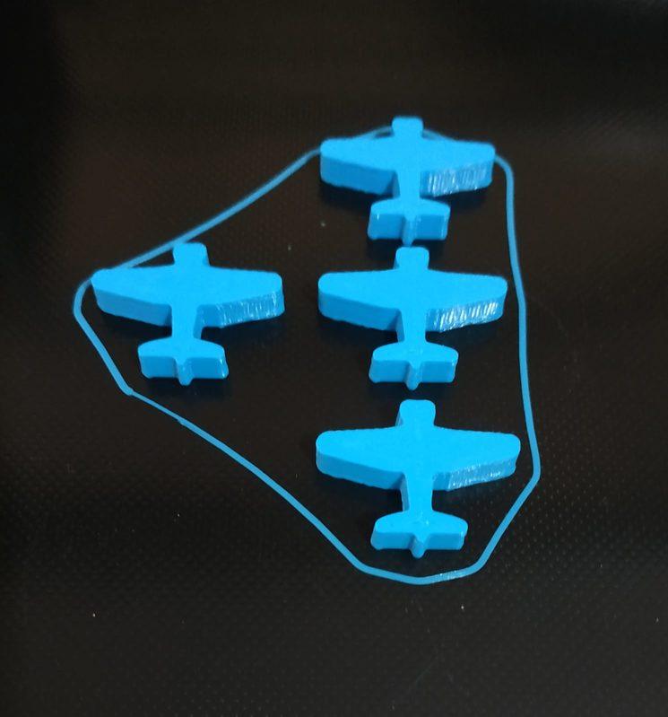 La máquina empieza a imprimir de 4 en 4. Esa línea alrededor de las figuras se llama falda y es un elemento que se hace para fundir el plástico inicial y lograr un flujo continuo en el resto de fichas.