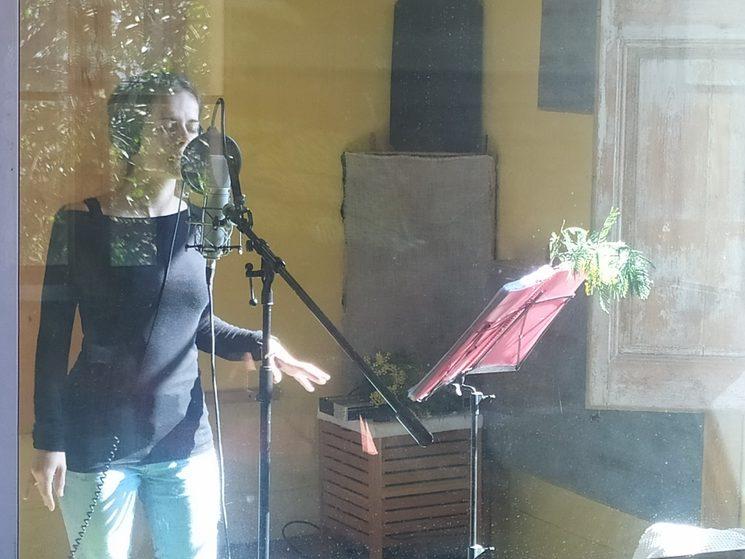 Meritxell cantant amb un ram de mimoses al faristol