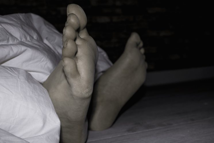 ...Una tenue luz de una vela irrumpe en la oscuridad. Una montaña de sábanas dejan entrever los pies descalzos...
