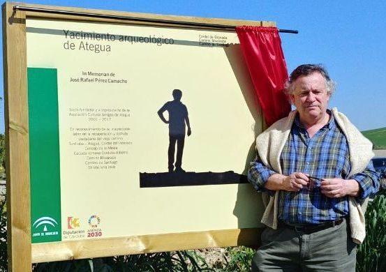 Manolo Cobos junto al cartel homenaje a Camacho en el cordel que comunica la ciudad de Ategua con Córdoba.