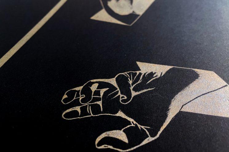 Detalle de la ilustración dorada sobre cartulina negra